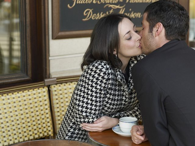 Couple kissing at outdoor cafe --- Image by © Les and Dave Jacobs/cultura/Corbis
