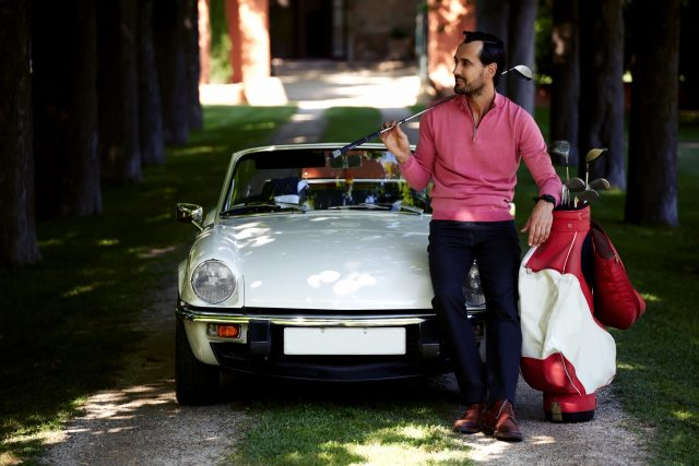 Handsome golf player holding a driver or golf club while getting ready for a day on the course, just arrived on his convertible luxury car wealthy man preparing for golf game at his recreation time